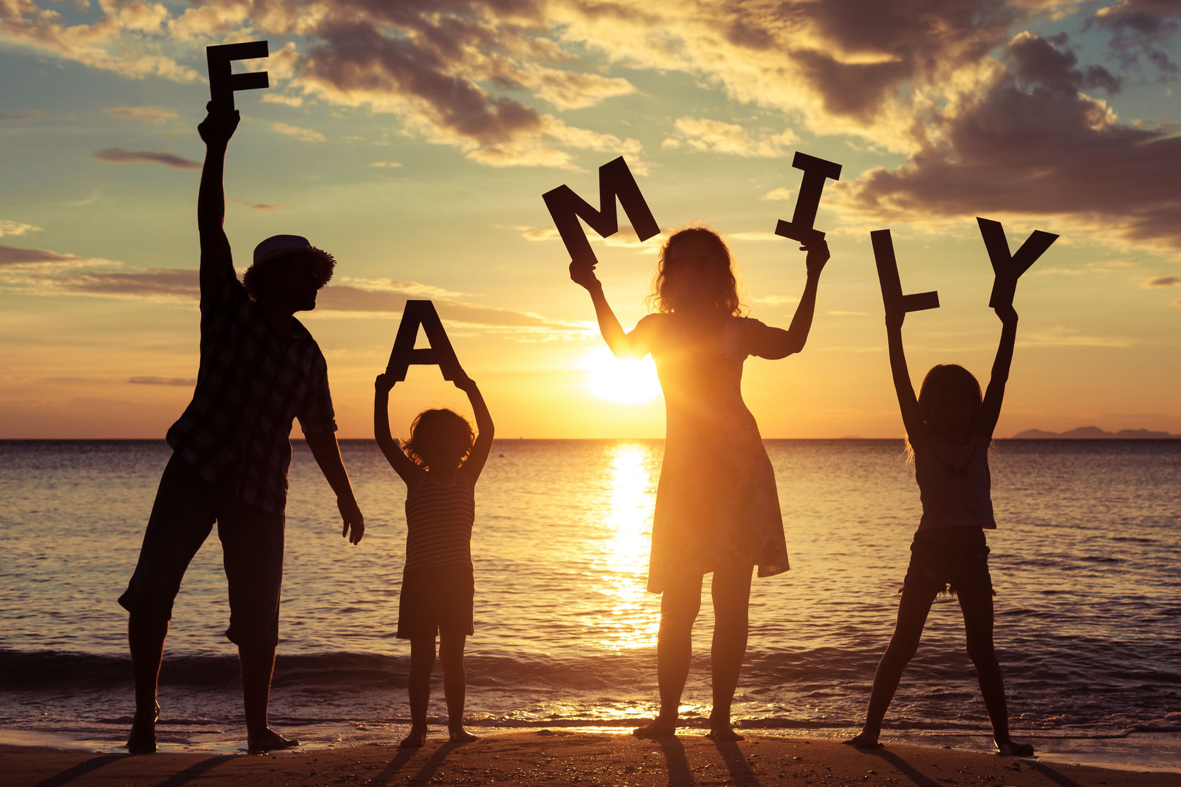 "44757397 - happy family standing on the beach at the sunset time. they keep the letters forming the word "" family"". concept of friendly family."