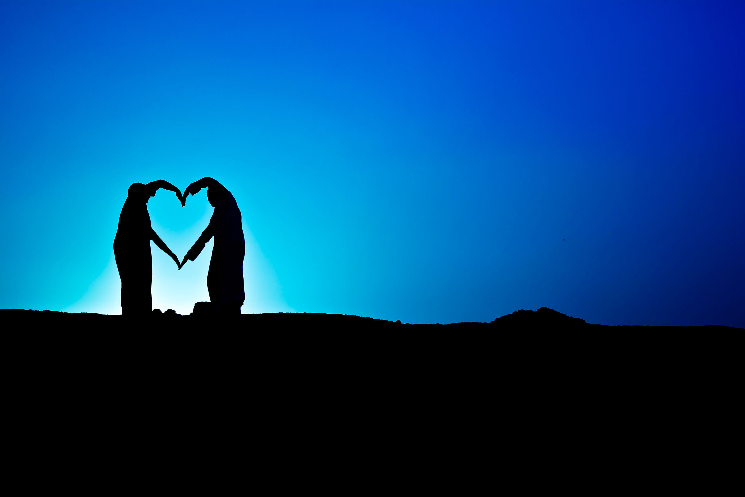 61861741 - conceptual heart shape, symbol of human. woman and man hand silhouette over sky at sunset background, metaphor to love, valentine day, romantic, couple, wedding, romance, summer or sunrise